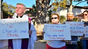 Protesters led by the Rev. Dermot P. Rodgers outside Immaculate Conception Catholic Church. Photo by Chris Stone